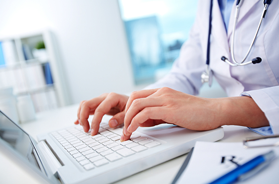 A medical professional typing on a laptop computer